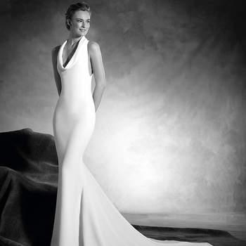 A personalidade e a elegância estiveram sempre muito unidas e isso o demonstra este moderno vestido de noiva sereia, realizado em crepe, de corte baixo e um espetacular decote halter, sem mangas.