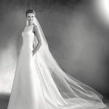 Arrojado vestido de noiva sem mangas de decote em barco e silhueta de corte em A. Um modelo de mikado de estilo clássico com volume na saia e práticos bolsos laterais. O detalhe: uma bonita fileira de botões nas costas destaca a silhueta da noiva.