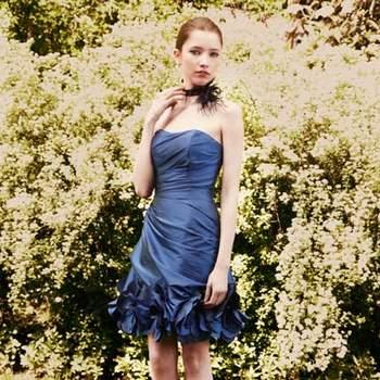Petite robe courte Pronuptia 2012 au décolleté légèrement plongeant tout en taffetas drapé asymétriquement. Le bas de la robe est souligné de grandes fleurs aux pétales virevoltants.