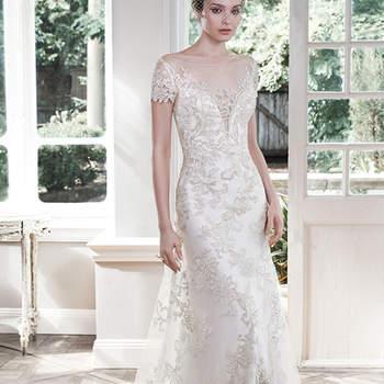 """Brilhantes apliques de renda metálicos cobrem o tule neste vestido de casamento glamouroso e vintage tipo linha A com decote ilusão profundo. Acabado com mangas curtas, botões de cristal e feche com zíper.  <a href=""""http://www.maggiesottero.com/dress.aspx?style=5MR605"""" target=""""_blank"""">Maggie Sottero</a>"""