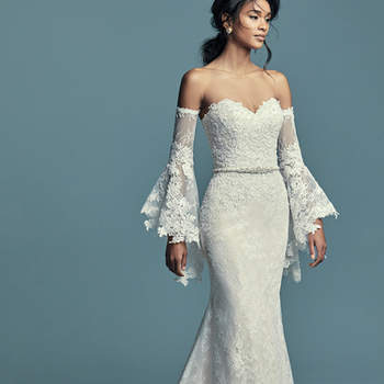 """<a href=""""https://www.maggiesottero.com/maggie-sottero/tenille/11509"""">Maggie Sottero</a>  Chic lace motifs dance over allover lace in this boho fit-and-flare wedding dress, accenting the bodice and breathtaking hem. Complete with strapless sweetheart neckline. Finished with zipper over inner corset closure, with covered buttons trailing from back to hem. Illusion lace poet sleeves sold separately. Detachable beaded belt accented in Swarovski crystals sold separately. Detachable illusion lace cap-sleeves can be worn on or off the shoulder, sold separately."""