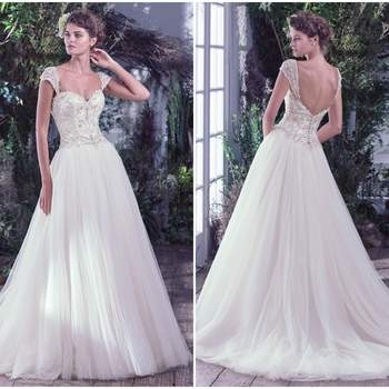"""Swarovski crystals, pearls, and embroidered lace adorn the fitted bodice and sweetheart neckline before flowing into a dreamy tulle ball gown skirt. Finished with covered buttons over zipper and inner corset closure. Detachable embellished cap-sleeves sold separately.  <a href=""""https://www.maggiesottero.com/maggie-sottero/beverly/9742"""" target=""""_blank"""">Maggie Sottero</a>"""