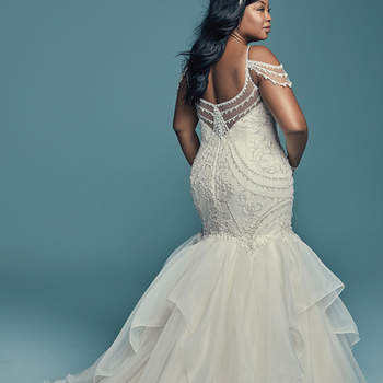 """<a href=""""https://www.maggiesottero.com/maggie-sottero/brinkley-lynette/11459"""">Maggie Sottero</a>  Glamorous and vintage-inspired, this mermaid wedding dress offers additional coverage to our original Brinkley style. The tulle bodice is accented in beaded embroidery and Swarovski crystals, while beaded illusion cold-shoulder sleeves complete the sweetheart neckline and V-back, also trimmed in beading and illusion. Fit-and-flare skirt comprised of tiered Chic Organza trimmed in horsehair. Finished with crystal buttons over zipper closure."""