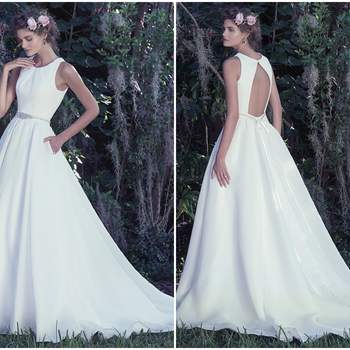"""This classic A-line wedding dress is elevated by fashion-forward elements including the use of rich Shavon organza, a dramatic open back, and pleated jewel neckline. Unadorned, this voluminous skirt features covered buttons trailing from waist to hemline and hidden pockets. Finished with covered buttons over zipper closure. Detachable beaded belt sold separately.   <a href=""""https://www.maggiesottero.com/maggie-sottero/anita/9730"""" target=""""_blank"""">Maggie Sottero</a>"""