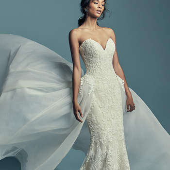 """<a href=""""https://www.maggiesottero.com/maggie-sottero/stephanie/11435"""">Maggie Sottero</a>  Elegant and romantic, this soft fit-and-flare wedding dress features allover lace motifs atop tulle, completing the strapless plunging sweetheart neckline. Lined with shapewear for a figure-flattering fit, and finished with covered buttons over zipper closure. Illusion off-the-shoulder cap-sleeves accented in lace motifs sold separately. Detachable tulle train accented in lace motifs sold separately."""