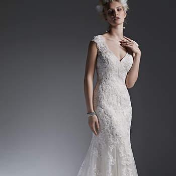 """Os apliques de renda adornam o tule neste vestido de casamento deslumbrantemente modificado no estilo evasê e com decote fechadura nas costas. Finaliza com botões forrados sobre o fechamento do zíper. <a href=""""https://www.maggiesottero.com/sottero-and-midgley/lydia/9577"""" target=""""_blank"""">Sottero and Midgley</a>"""