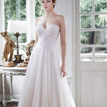 "Simplistic elegance is found in this stunning tulle A-line wedding dress, accented with delicate asymmetrical lace appliqués cascading down the bodice. Finished with sweetheart neckline and covered buttons over zipper with inner elastic closure.  <a href=""http://www.maggiesottero.com/dress.aspx?style=5MT699"" target=""_blank"">Maggie Sottero</a>"