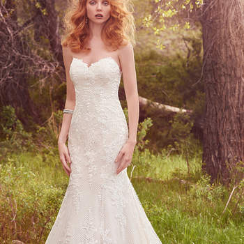 "Lovely lace appliqués cascade over crosshatch tulle in this classic fit-and-flare, featuring an exquisite lace hem, lace illusion back, sweetheart neckline, and tear-drop shaped train. Finished with covered buttons over zipper closure. <a href=""https://www.maggiesottero.com/maggie-sottero/makenna/10121?utm_source=mywedding.com&amp;utm_campaign=spring17&amp;utm_medium=gallery"" target=""_blank"">Maggie Sottero</a>"