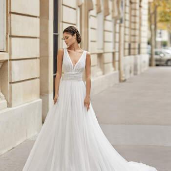 Ideal para uma cerimónia civil romântica e primaveril, o vestido Tinek estilo princesa combina uma saia de tule fluida e longa cauda, corpete de renda e alças largas. Decote deep-plunge até às costas abertas, com rendas na cintura. | Rosa Clará 2021