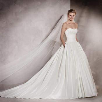 Todas já sonhámos com um vestido de noiva princesa de tafetá como este. Romântico e repleto de feminilidade. Este desenho com decote em coração e corte na cintura vestem uma noiva de conto de fadas.