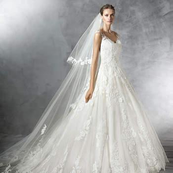 Soberbo vestido de noiva de tule com decote em bico e saia de corte em A. Um modelo decorado com motivos florais de renda e guipura que percorrem todo o corpo conferindo-lhe feminilidade.