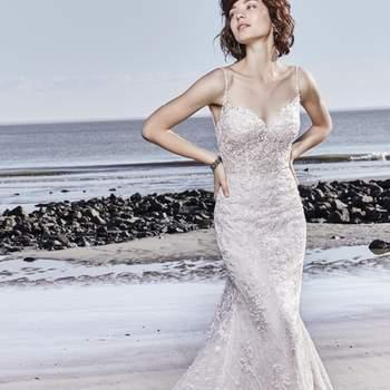 """<a href=""""https://www.maggiesottero.com/sottero-and-midgley/marcelle/11553"""">Maggie Sottero</a> <br> Cette robe de mariée fourreau est ornée de magnifiques motifs en dentelle. Ses bretelles fines perlées relient le décolleté en cœur au dos nu."""