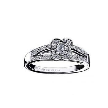 Cette splendide bague de fiançailles ne pourra plus vous quitter. Un diamant (0,10 carat de qualité HSI) est serti au centre sur 4 griffes. Le corps de bague aux lignes fines et épurées met en valeur le diamant. Source : mauboussin.fr