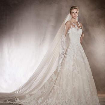 A renda e os detalhes florais dão forma a este vestido de noiva de decote em coração. O tule e as aplicações percorrem todo o vestido chegando a fundir-se com a pele. Um vestido muito romântico que se desenha sobre o corpo da noiva transformando-a em princesa por um dia.