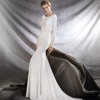 Esplêndido vestido de noiva com decote em barco e manga comprida estilo sereia que embeleza a silhueta feminina. Uma sublime criação de crepe, chantilly, guipura e tule com motivos florais.