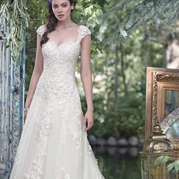"""Glittering lace appliqués, sweetened with Swarovski crystals, drape the bodice of this elegant tulle A-line wedding dress, with an exquisite lace-lined hem. Finished with sweetheart neckline and corset closure. Detachable lace cap-sleeves sold separately. <a href=""""https://www.maggiesottero.com/maggie-sottero/laverna/9525"""" target=""""_blank"""">Maggie Sottero</a>"""