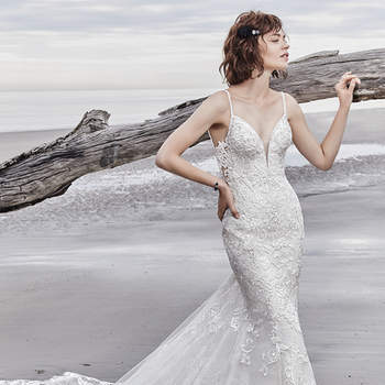 "Elegant lace motifs dance over tulle in this relaxed fit-and-flare wedding dress, trimming the illusion  side panels, and V-neckline. Beaded spaghetti straps create a unique double-crisscross effect in the open back.  Finished with covered buttons over zipper closure.  <a href=""https://www.maggiesottero.com/sottero-and-midgley/sullivan/11569"">Sottero and Midgley</a>"
