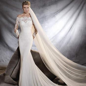 Deslumbrante vestido de noiva vaporoso de gaza e tule, com corte na cintura e mangas três quartos. Uma obra artesanal única com delicados motivos de renda no decote envolvente. Pura elegância.
