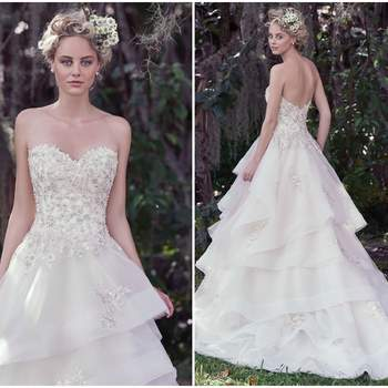 """Romantic and sophisticated, this fitted bodice, adorned with beaded floral appliqués and Swarovski crystal details, falls into a voluminous layered horsehair edged skirt. The soft sweetheart neckline adds an extra dose of femininity to this modern tulle and Chic organza ball gown wedding dress. Finished with covered buttons over zipper and inner corset closure.   <a href=""""https://www.maggiesottero.com/maggie-sottero/katherine/9699"""" target=""""_blank"""">Maggie Sottero</a>"""