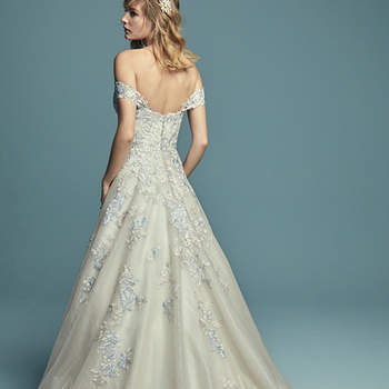 """<a href=""""https://www.maggiesottero.com/maggie-sottero/maine/11494"""">Maggie Sottero</a>  Gorgeous colored lace motifs dance over the bodice of this wedding dress, adding dimension to the A-line skirt comprised of textured, shimmering tulle. Complete with strapless sweetheart neckline and attached beaded belt accented in Swarovski crystals. Finished with crystal buttons over zipper and inner elastic closure. Illusion lace cap-sleeves can be worn on or off the shoulder, sold separately."""