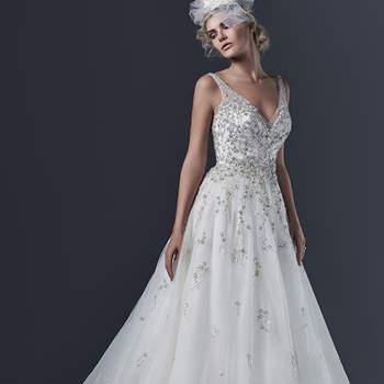 """O efeito etéreo do tule cria um vestido moderno e deslumbrante, adornado com cristais Swarovski e rendas brilhantes. Um decote profundo na frente e nas costas completa o look. Acabamento com botões de cristal e zíper.  <a href=""""http://www.sotteroandmidgley.com/dress.aspx?style=5SR600"""" target=""""_blank"""">Sottero and Midgley</a>"""