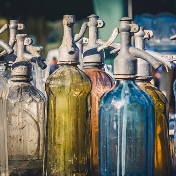 Centro de mesa de boda con botellas de cristal