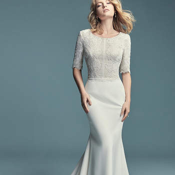"""<a href=""""https://www.maggiesottero.com/maggie-sottero/edalene/11468"""">Maggie Sottero</a>  This modest sleeved wedding dress features an allover lace bodice with elegant elbow-length sleeves and a scoop neckline. Soft sheath skirt is comprised of Aldora Crepe. Finished with zipper closure."""