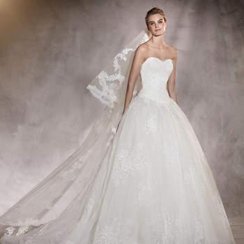 Um vestido de noivas de sonho realizado em organza, chantilly, fio bordado e pedraria. Um desenho com cintura baixa com decote em coração que transformam a noiva na autêntica protagonista do seu dia.