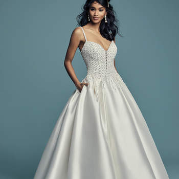 """<a href=""""https://www.maggiesottero.com/maggie-sottero/dana/11464"""">Maggie Sottero</a>  Delicate beaded motifs adorn the bodice of this Elodie Mikado princess wedding dress, drifting into a billowing ballgown skirt with pockets. Beaded spaghetti straps complete the illusion plunging sweetheart neckline. Finished with crystal buttons over zipper closure."""