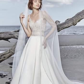 """<a href=""""https://www.maggiesottero.com/sottero-and-midgley/saylor/11566"""">Maggie Sottero</a> <br> Une robe de mariée princesse avec des détails bohème qui comporte un corsage de dentelle transparente perlé orné de cristaux de Swarovski prolongé par une jupe en satin."""