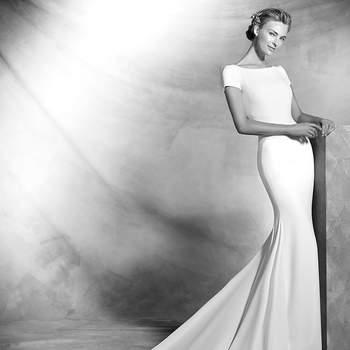 Vestido simples de noiva em crepe, estilo sereia, de manga curta. Corpo com decote em barco na frente e grande abertura central nas costas.