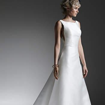"""Este modelo dramático e estruturado. Trata-se de um vestido de noiva evasê em mikado, com decote canoa sofisticado e que rouba a cena com as costuras laterais, bolsos escondidos e deslumbrante decote nas costas. Finaliza com botões forrados sobre o fechamento do zíper.  <a href=""""https://www.maggiesottero.com/sottero-and-midgley/mccall/9592"""" target=""""_blank"""">Sottero and Midgley</a>"""