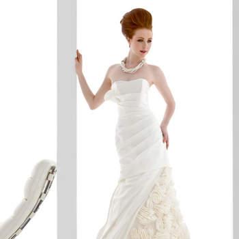 abito sposa di linea a sirena in raso con motivo assimmetrico col fondo gonna e rose in tessuto.