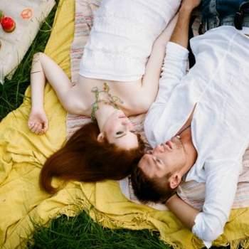 Romántica foto de los novios tumbados en el cesped.