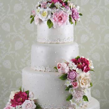 Una tarta romántica y clásica que reproduce en azúcar las flores del ramo de la novia rosas peonías tulipanes y jazmines cubierta de perlas y detalle de encaje en azúcar.