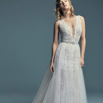 """<a href=""""https://www.maggiesottero.com/maggie-sottero/hailey-marie/11269"""">Maggie Sottero</a>  Lace motifs cascade over crosshatch and tulle in this unique fit-and-flare wedding gown, completing the bodice and illusion skirt. Featuring an illusion plunging V-neckline, straps, and square back, and lined with inner bodysuit for a flattering fit. Finished with covered buttons over zipper closure. Detachable tulle overskirt accented with an attached beaded belt sold separately."""