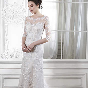 "A dramatic illusion lace back and illusion sleeves adorn this hand-embellished sheath gown, glimmering with metallic lace appliqués and embroidered with Swarovski crystals drifting from shoulder to floor-skimming hem. A delicate scalloped hemline completes the look. Finished with pearl button over zipper back closure. <a href=""http://www.maggiesottero.com/dress.aspx?style=5MW113&amp;page=0&amp;pageSize=36&amp;keywordText=&amp;keywordType=All"" target=""_blank"">Maggie Sottero</a>"