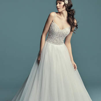 """<a href=""""https://www.maggiesottero.com/maggie-sottero/lucca/11281"""">Maggie Sottero</a>  This princess wedding dress features a bodice of beaded embroidery, accented in Swarovski crystals. Ballgown skirt comprised of tulle and trimmed in horsehair. Beaded straps complete the soft V-neckline and scoop back. Finished with pearl buttons over zipper closure."""