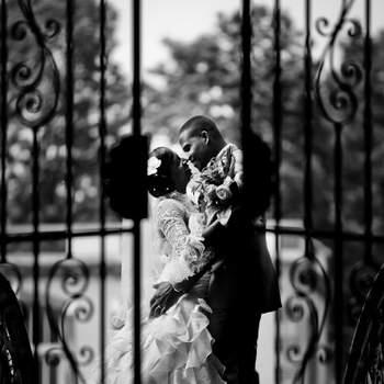 """Le mot du photographe : Rose & Emmanuel se sont mariés le 19 Mai 2012, à Lardy dans le 91.  Elle travaille dans les ressources humaines, lui est sous-officier de l'armée de terre.  Il se sont dit """"oui"""" dans la petite église du village, puis la réception s'est déroulée dans un château à quelques kilomètres de là. Ce cliché est issu de leur séance photo de couple, réalisée quelques jours après le mariage, dans le jardin du château de la réception. Une fois le stress et la pression du Jour-J passés, nous nous sommes donnés le temps de faire une belle séance, agréable pour eux aussi, en écoutant leurs idées, leurs envies. C'est une organisation que l'on recommande systématiquement à nos mariés, car cela participe à notre démarche qualité.  Ce que l'on aime sur cette photo, c'est la douceur des attitudes, les deux regards chargés d'amour. Le portail entre-ouvert donne un coté indiscret à la scène, tout en donnant de la symétrie à la composition.  Si cette photo est selon vous, LA PLUS BELLE PHOTO DE MARIAGE, laissez un commentaire ci-dessous en indiquant le n°3"""