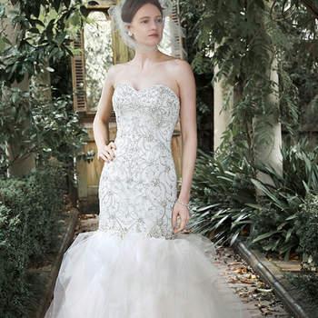 """Cristais Swarovski, pérolas e lantejoulas adornam o corpete deste ajustado vestido de noiva, com saia de tule. Disponível com laço, capa e luvas opcionais. Acabado com botões de cristal e de zíper e feche no espartilho interior.   <a href=""""http://www.maggiesottero.com/dress.aspx?style=5MT710"""" target=""""_blank"""">Maggie Sottero</a>"""