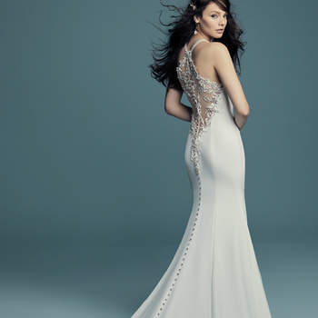 """<a href=""""https://www.maggiesottero.com/maggie-sottero/maurelle/11496"""">Maggie Sottero</a>  Swarovski crystals and beaded lace motifs cascade along the illusion plunging keyhole neckline and illusion halter back in this sexy wedding dress, comprised of Aldora crepe. Crystal buttons drift from zipper to hemline."""