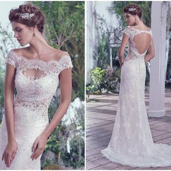 """Embroidered and beaded illusion lace featuring Swarovski crystals adds drama and dimension to this bateau neckline, off-the-shoulder sleeves, and illusion waistline. An elegant train falls behind this sheath silhouette. Finished with a statement making keyhole back and pearl buttons over zipper closure.   <a href=""""https://www.maggiesottero.com/maggie-sottero/sipriana/9709"""" target=""""_blank"""">Maggie Sottero</a>"""