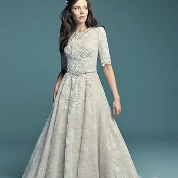 """<a href=""""https://www.maggiesottero.com/maggie-sottero/annabella-marie/11454"""">Maggie Sottero</a>  This modest sleeved wedding dress is comprised of allover lace, with striking lace motifs accenting the bodice, jewel neckline, and half sleeves. Lace motifs trail from back to hem in the A-line skirt. Finished with zipper closure."""