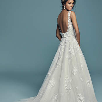 """<a href=""""https://www.maggiesottero.com/maggie-sottero/meryl-lynette/11282"""">Maggie Sottero</a>  This vintage-inspired ballgown features lace appliqués over whimsical layers of textured tulle and Chic organza. Featuring a V-neckline, illusion straps accented with lace appliqués, and square back. Swarovski crystals and beading add shimmer and ethereal texture. Finished with covered buttons over zipper closure. Detachable beaded belt featuring Swarovski crystals sold separately."""