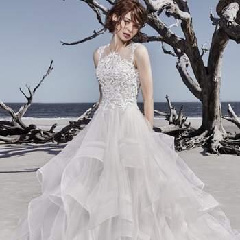 """<a href=""""https://www.maggiesottero.com/sottero-and-midgley/ariya/11516"""">Maggie Sottero</a> <br> Cette robe de princesse moderne se compose d'un corsage en dentelle perlé, rdécoré de cristaux Swarovski, sur une jupe en tulle faite de plusieurs volants."""