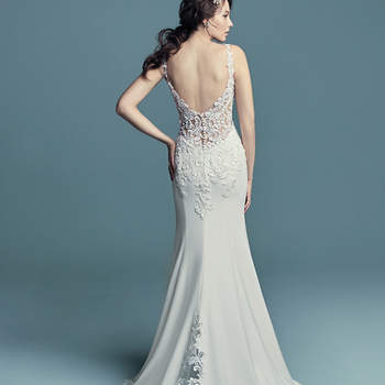 """<a href=""""https://www.maggiesottero.com/maggie-sottero/alaina/11453"""">Maggie Sottero</a>  Embroidered lace motifs accented in pearls and Swarovski crystals cascade over the sheer bodice of this romantic Aldora Crepe wedding dress, completing the straps, V-neckline, and illusion scoop back. Sheath skirt features an illusion cutout train accented in lace motifs and an attached beaded belt with Swarovski crystals. Finished with pearl buttons and zipper closure."""