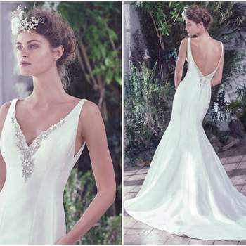 """Structured Elodie mikado wedding dress with stylized seams dramatically flares to create a refined fit and flare silhouette. The deep V-neckline and open back are embellished with crystals and beads for added luxury and dimension. Finished with crystal buttons over zipper closure.   <a href=""""https://www.maggiesottero.com/maggie-sottero/roan/9750"""" target=""""_blank"""">Maggie Sottero</a>"""