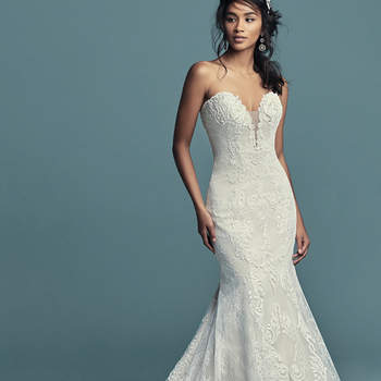 """<a href=""""https://www.maggiesottero.com/maggie-sottero/freida/11474"""">Maggie Sottero</a>  This soft yet alluring fit-and-flare features alternating sections of allover lace along the sides and cascades of lace motifs and crosshatching down the middle. An illusion plunging neckline completes the elegance of this strapless tulle wedding dress. Finished with inner corset and covered buttons over zipper closure."""