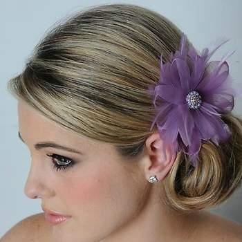 Une fleur de couleur dans un chignon bas, voilà la touche vintage qu'il vous faut ! - Source : www.maritzasbridal.com