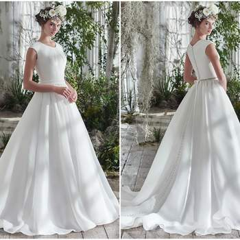 """Rich Shavon organza adds an exquisite dose of romantic elegance to this voluminous A-line wedding dress, detailed with covered buttons trailing from neck to hemline. Finished with cap-sleeves, soft scoop pleated neckline, hidden pockets, and covered buttons over zipper closure. Detachable beaded belt sold separately.   <a href=""""https://www.maggiesottero.com/maggie-sottero/anita-marie/9768"""" target=""""_blank"""">Maggie Sottero</a>"""
